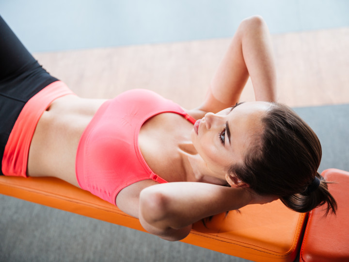 Focused pretty young sportswoman doing abs crunches on bench in gym